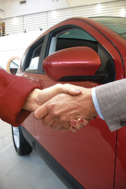 A man and woman shake hands in front of a car.